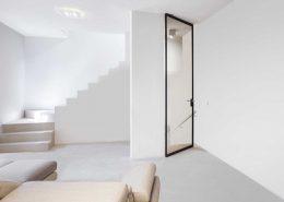 porta a bilico con struttura in allumino in finitura Testa di Moro, vetro Bronzo Trasparente e adattatore rettangolare per maniglie tradizionali in alluminio nella stessa finitura della porta.